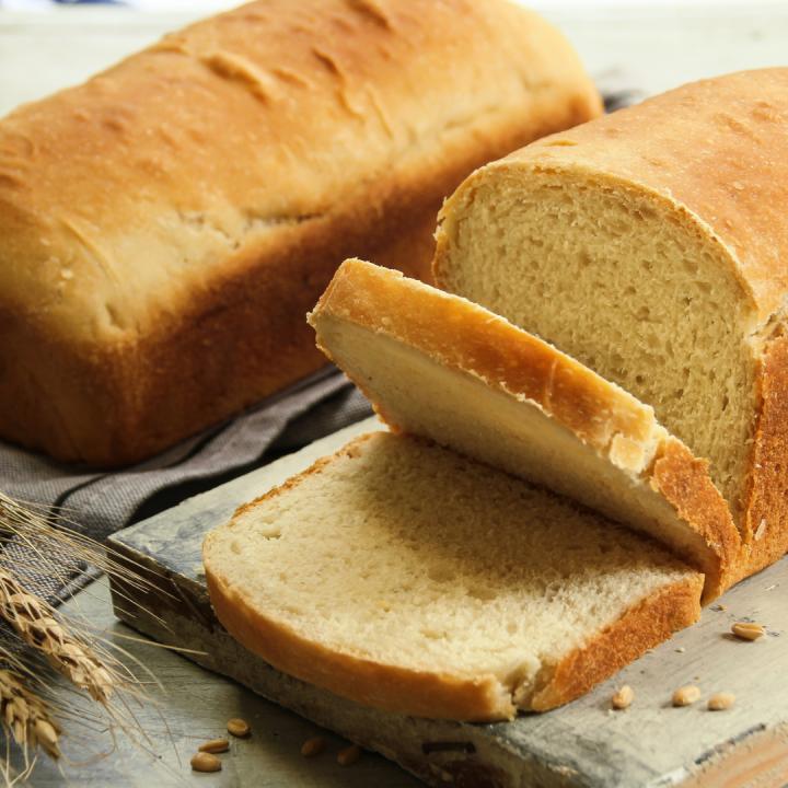 laof of white bread cut on board