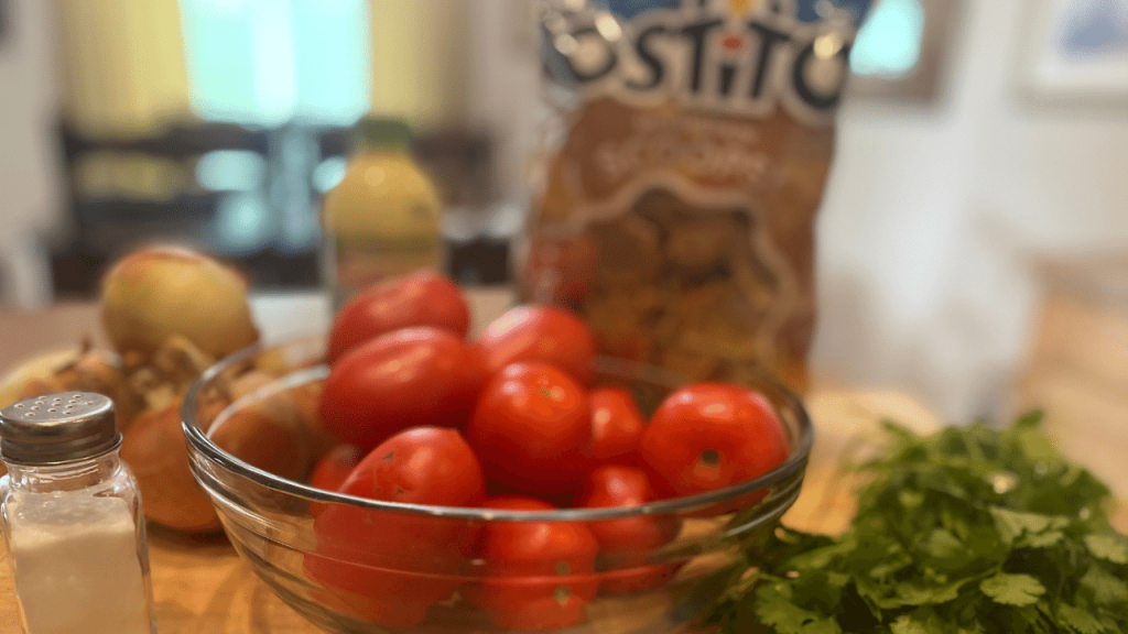 fresh salsa ingredients on cutting board, tomatoes, onions, cilantro, chips