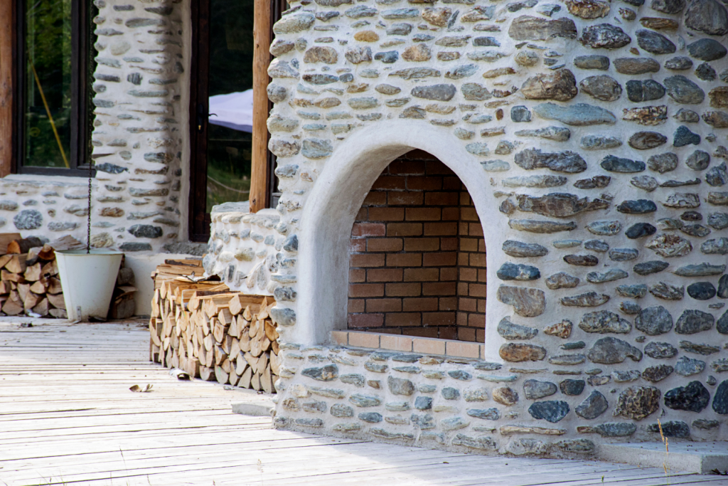outside fireplace with wood chopped in piles