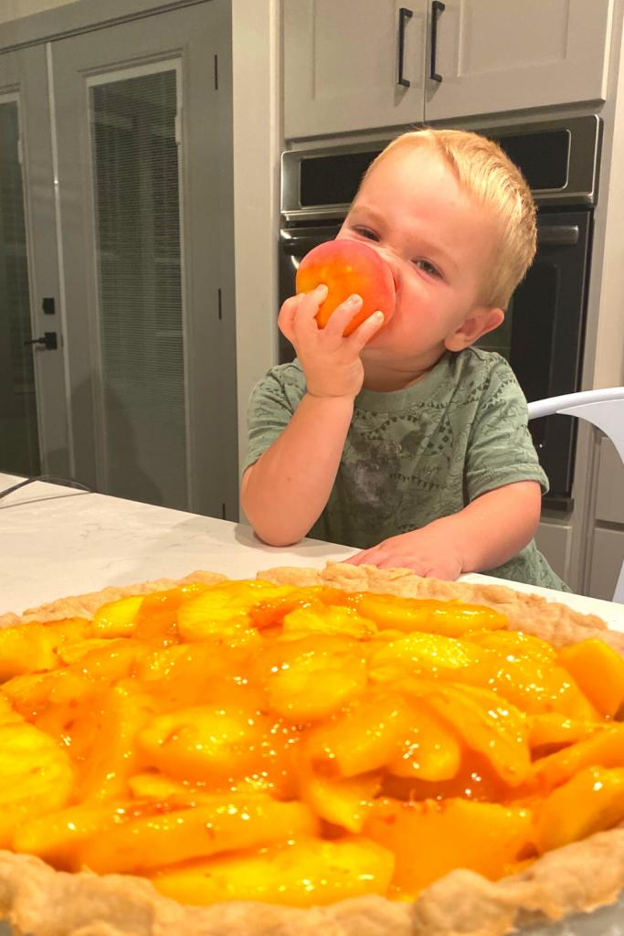 boy eating peach with a fresh peach pie